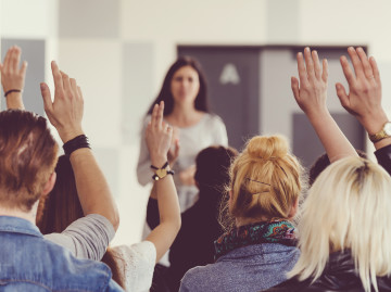 Audience with hands raised facing female speaker