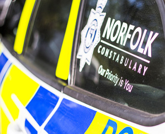Side of police car with Norfolk Constabulary logo